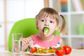 Cute little girl eats vegetable salad using fork Royalty Free Stock Photo