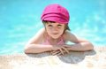 Cute little girl on the edge of swimming pool Stock Images