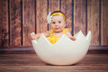 Cute little girl in the egg basket. Royalty Free Stock Photo