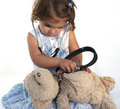 Cute little girl examining teddy Royalty Free Stock Image