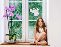 Cute little girl with flower sitting on windowsill of new pvc wi Royalty Free Stock Photo