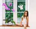Cute little girl with flower sitting on windowsill of new pvc wi children safety concept Royalty Free Stock Image