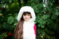 Cute little girl in fur coat under rowan tree Royalty Free Stock Photos