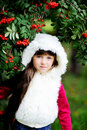 Cute little girl in fur coat under rowan tree Stock Image