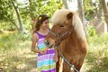 Cute little girl giving her pony a carrot is Stock Image