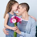 Cute little girl giving mom bouquet of pink gerbera daisies. Loving mother and daughter smiling and hugging. Royalty Free Stock Photo