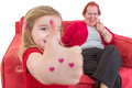 Cute little girl giving a thumbs up gesture with red hearts painted on her hand is of approval her grandmother who is seated on Royalty Free Stock Images