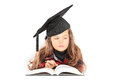 Cute little girl with graduation hat reading a book isolated on white background Stock Photos