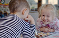 Cute little girl grinning at her brother mischievously as they sit a table together playing a game of checkers or draughts Royalty Free Stock Photography