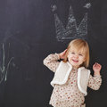 Cute little girl having fun chalk drawing on dark background Stock Image