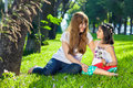 Cute little girl with her loving mother sitting barefoot on lush green spring grass in the shade of large trees smiling into each Stock Image