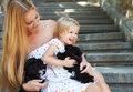 Cute little girl and her mother hugging dog puppies friendship care concept Royalty Free Stock Image