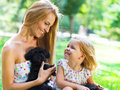 Cute little girl and her mother hugging dog puppies friendship care concept Stock Photo