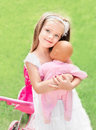 Cute little girl with her toy carriage and doll embracing outdoors Royalty Free Stock Photos