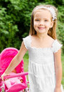 Cute little girl with her toy carriage and doll outdoors Stock Images