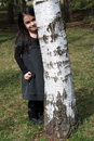 Cute little girl hiding behind birch in park Stock Image