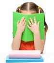 Cute little girl is hiding behind a book