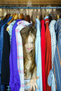 Cute little girl hiding inside wardrobe from her parents early morning Stock Photo