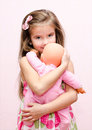 Cute little girl holding and embracing her doll Royalty Free Stock Photo