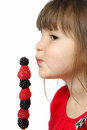 Cute little girl holding kabob raspberries blackberries Royalty Free Stock Images