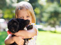 Cute little girl hugging dog puppy outdoors friendship and care concept Royalty Free Stock Photo
