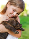 Cute little girl hugging her dog puppy sunny day friendship and care concept Stock Photography