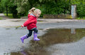 Cute little girl jumping very in red jacket blue jeans and rubber boots is over a puddle on a rainy day Stock Images
