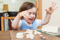 Cute little girl learning to sculpt dough figurines in the room Royalty Free Stock Image