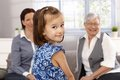 Cute little girl looking over shoulder smiling mother and grandmother at background Stock Images
