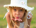 Cute little girl on the meadow blowing a kiss Royalty Free Stock Images