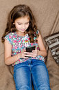 Cute little girl with mobile phone sitting on the sofa Royalty Free Stock Photo