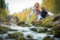 Cute little girl and mother sitting on a rock in autumn forest at stream Royalty Free Stock Photo
