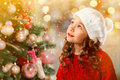 Cute little girl near Christmas tree. New Year card