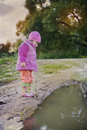 Cute little girl near a puddle Royalty Free Stock Photo