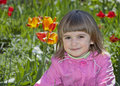 Cute little girl outdoor smiling in a pink cout near the flowers portrait Royalty Free Stock Photography