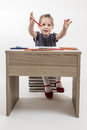 Cute little girl painting on blond a school desk in front of white background Royalty Free Stock Photos