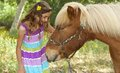 Cute little girl petting her pony a is giving a pet on his muzzle he has his eyes closed enjoying the attention Stock Photography