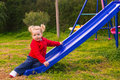 Cute little girl with pigtails playing in the garden adorable small funny is sitting on a slide Stock Photo