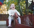 Cute little girl at playground swinging Stock Photo