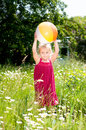 Cute little girl playing with a ball on a meadow blond in red summer dress is beach full of blooming daisies Stock Photos