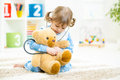 Cute little girl playing doctor with plush toy at kid home Stock Images