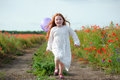 Cute little girl playing in a field with balloon. Summer poppy f Royalty Free Stock Photo