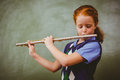 Cute little girl playing flute in classroom portrait of Stock Photo