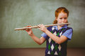 Cute little girl playing flute in classroom portrait of Royalty Free Stock Photo