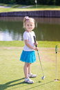 Cute little girl playing golf on a field Royalty Free Stock Photo