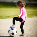 Cute little girl plays football Royalty Free Stock Photo