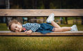 Cute little girl pleasure lying on bench in a park repose or relaxing in the nature Royalty Free Stock Image