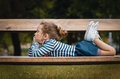 Cute little girl pleasure lying on bench in a park repose or relaxing in the nature Stock Photos