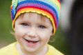Cute little girl portrait with rainbow hat outdoors Royalty Free Stock Photography