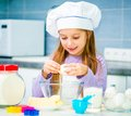 Cute little girl preparing cookies in the kitchen Royalty Free Stock Photo